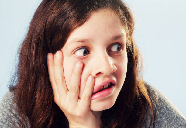 Shocked 12-year-old girl, hand to face, looks to the side A cute  pre-teen girl pulls at her face, looking wide-eyed to the side, shocked by something she sees. rolling eyes stock pictures, royalty-free photos & images