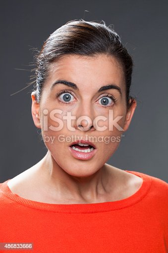 surprise and disappointment concept - portrait of a 30s brunette woman astonished and confused,studio shot,black background
