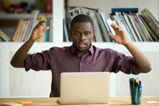Shocked african american office worker looking at laptop screen. Shocked young african american office worker looking at laptop screen throwing arms in the air. Horrified small business owner sees app error, lost documents because of unexpected bad computer crash. shocked computer stock pictures, royalty-free photos & images