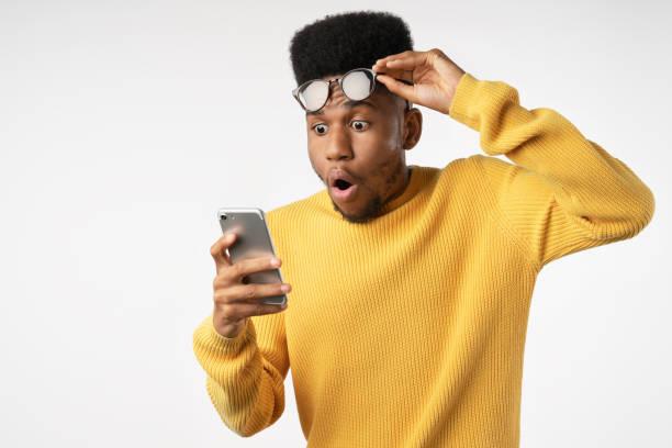 homem africano chocado enquanto assistia em smartphone em fundo branco isolado - excitação - fotografias e filmes do acervo