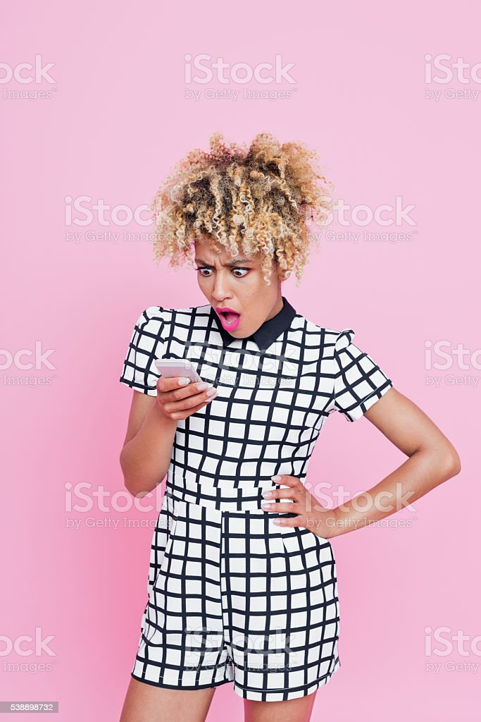 Shocked Afro Young Woman on Phone Portrait of shocked afro american woman wearing grid check playsuit looking on her cell phone with mouth open. Studio shot, pink background. Adult Stock Photo