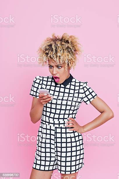 Shocked Afro Young Woman On Phone Stock Photo - Download Image Now