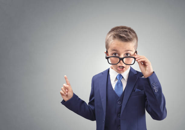 Shocked and surprised young confident executive businessman boy stock photo