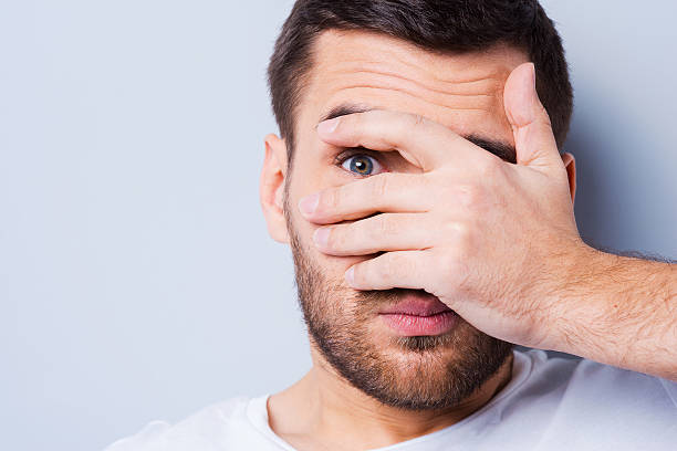 Shocked and terrified. Portrait of young man covering his face by hand and looking at camera while standing against grey background head in hands stock pictures, royalty-free photos & images