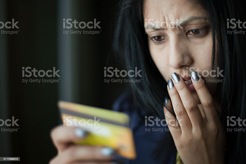 Shocked and worried young woman looking at credit card. stock photo