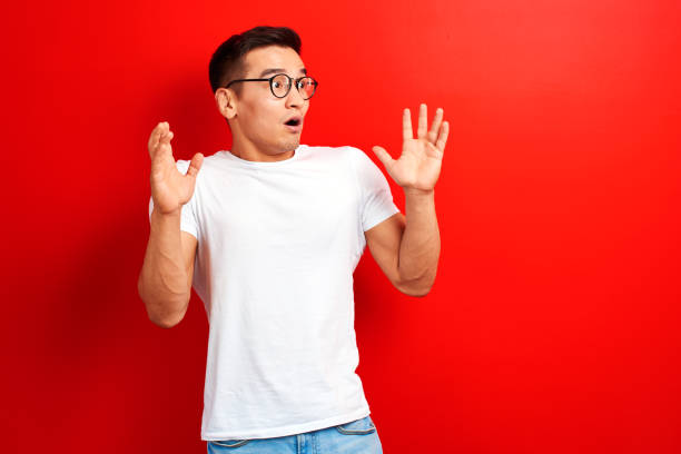 Shocked Asian man dressed in white casual and glasses with open mouth and hands up looks to the side. Surprised young Kazakh student guy on red studio background