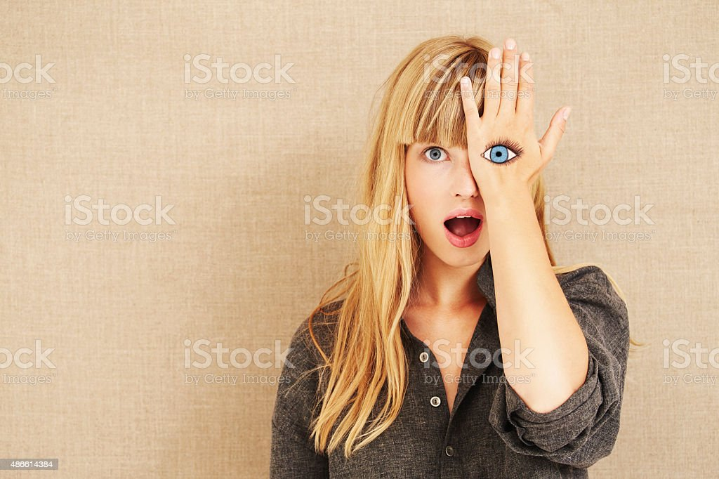 Shocked blond with painted eye stock photo