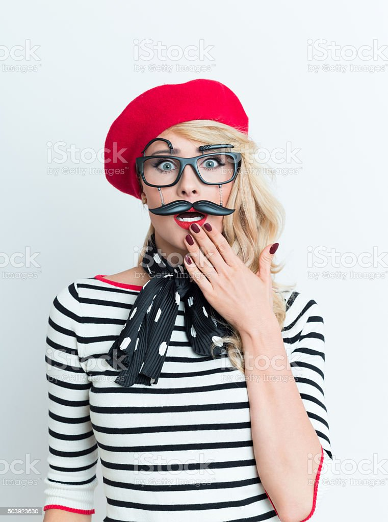 Shocked blonde french woman wearing red beret and facial mask Portrait of playful blonde woman in french outfit, wearing a red beret, striped blouse, neckerchief and funny facial mask, staring at camera with hand on chin. Adult Stock Photo