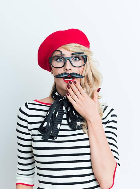 Chocado francesa mulher loira vestindo red beret e máscara facial - foto de acervo