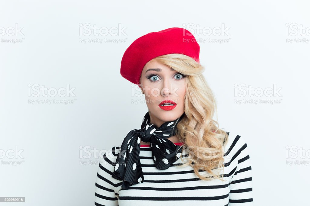 Shocked blonde french woman wearing red beret Portrait of shocked beautiful blonde woman in french outfit, wearing a red beret, striped blouse and neckerchief, staring at camera, rolling her eyes. Adult Stock Photo