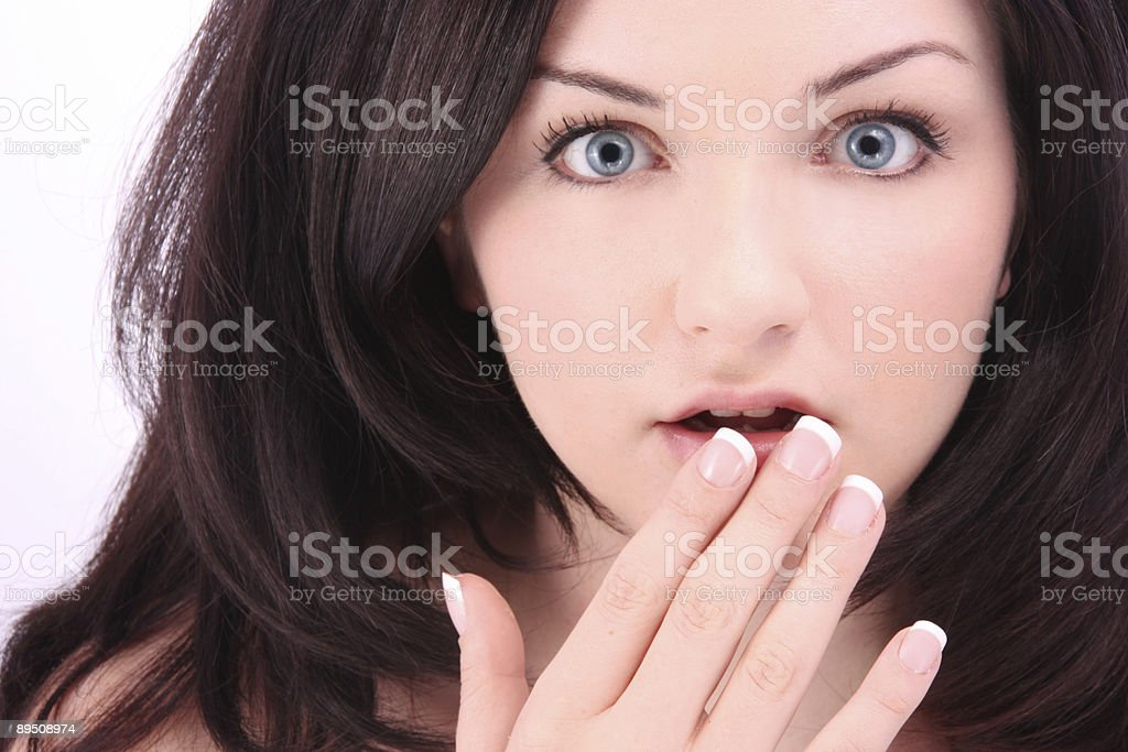 Shocked brunette with hand to mouth royalty-free stock photo