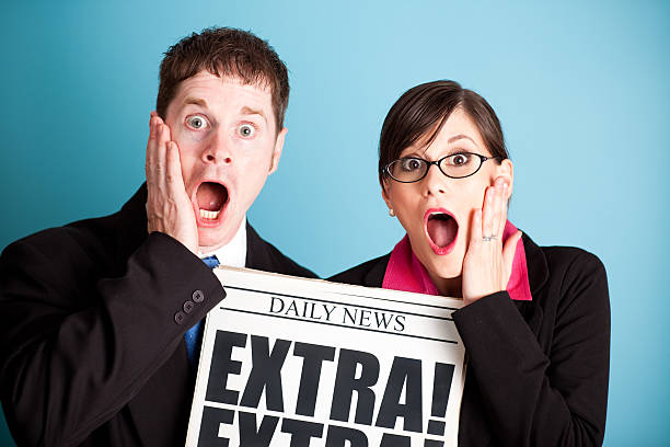 Shocked Business Man and Woman Holding Extra! Headline Newspaper Color photo of a young businessman and woman in suits holding a daily newspaper headlined
