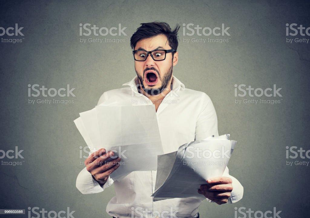 Schockiert Geschäftsmann Papiere mit Rechnungen durchsehen – Foto