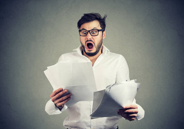 Shocked business man looking through papers with bills stock photo