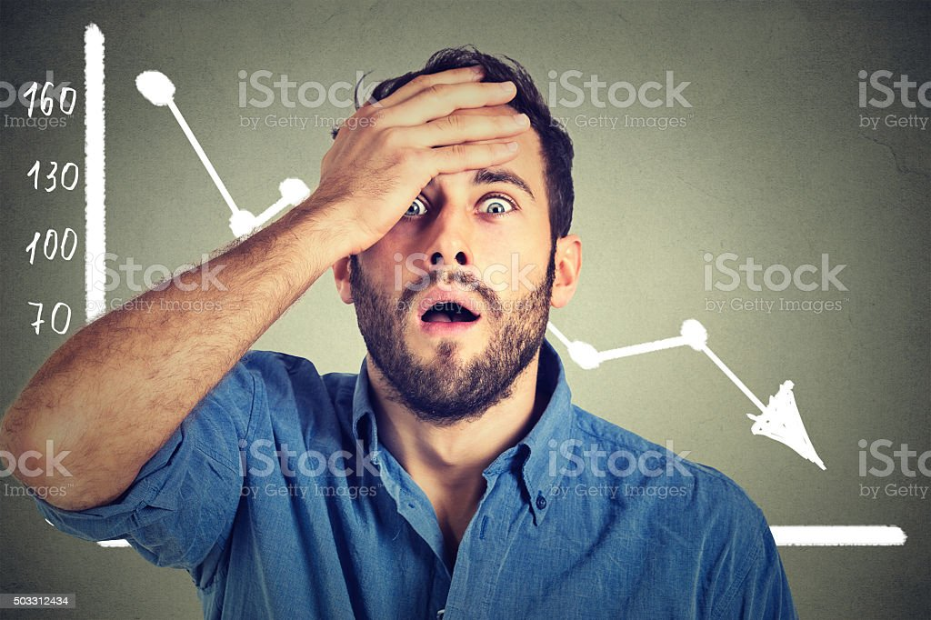 shocked business man with financial market chart graphic going down stock photo
