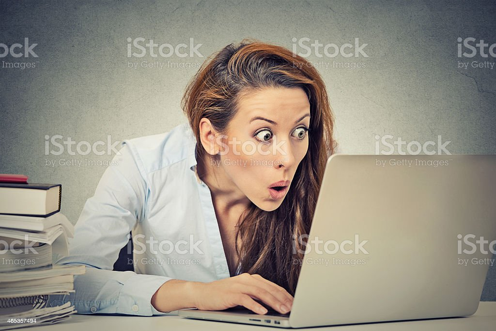 shocked business woman sitting in front of laptop computer stock photo