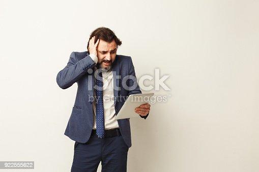 istock Shocked businessman looking at digital tablet 922555622