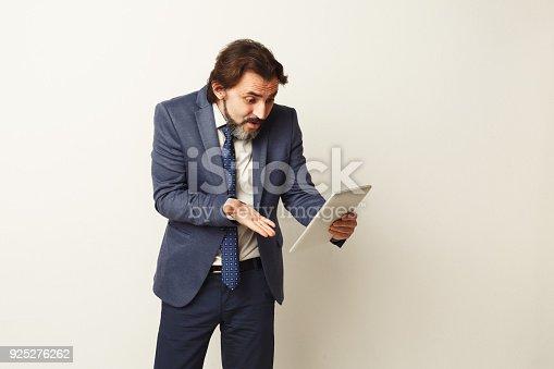 istock Shocked businessman looking at digital tablet 925276262