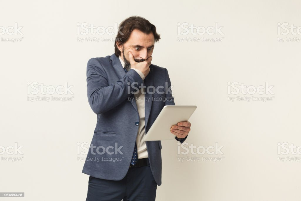 Shocked businessman looking at digital tablet royalty-free stock photo