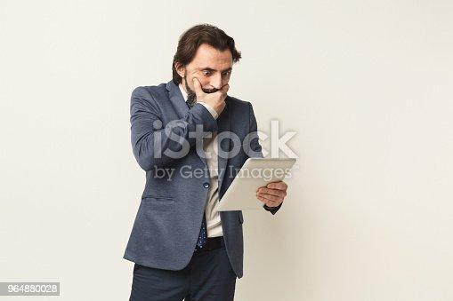 istock Shocked businessman looking at digital tablet 964880028