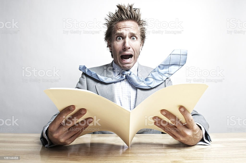 Shocked Businessman Office Worker Opening File Folder at Desk stock photo
