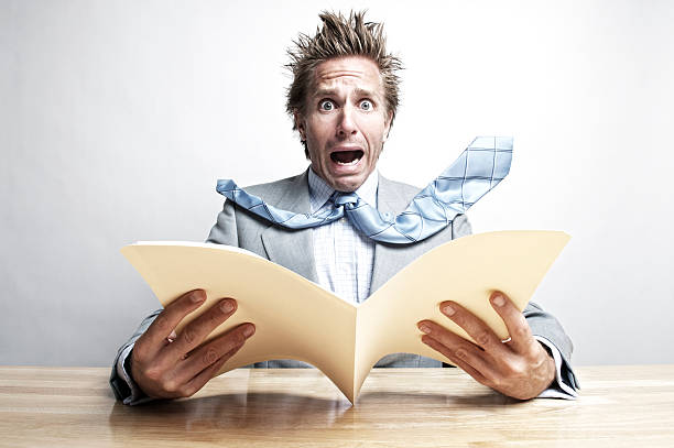 Shocked Businessman Office Worker Opening File Folder at Desk Office worker looks at the camera with expression of fear as he opens a file folder at his desk spiked stock pictures, royalty-free photos & images