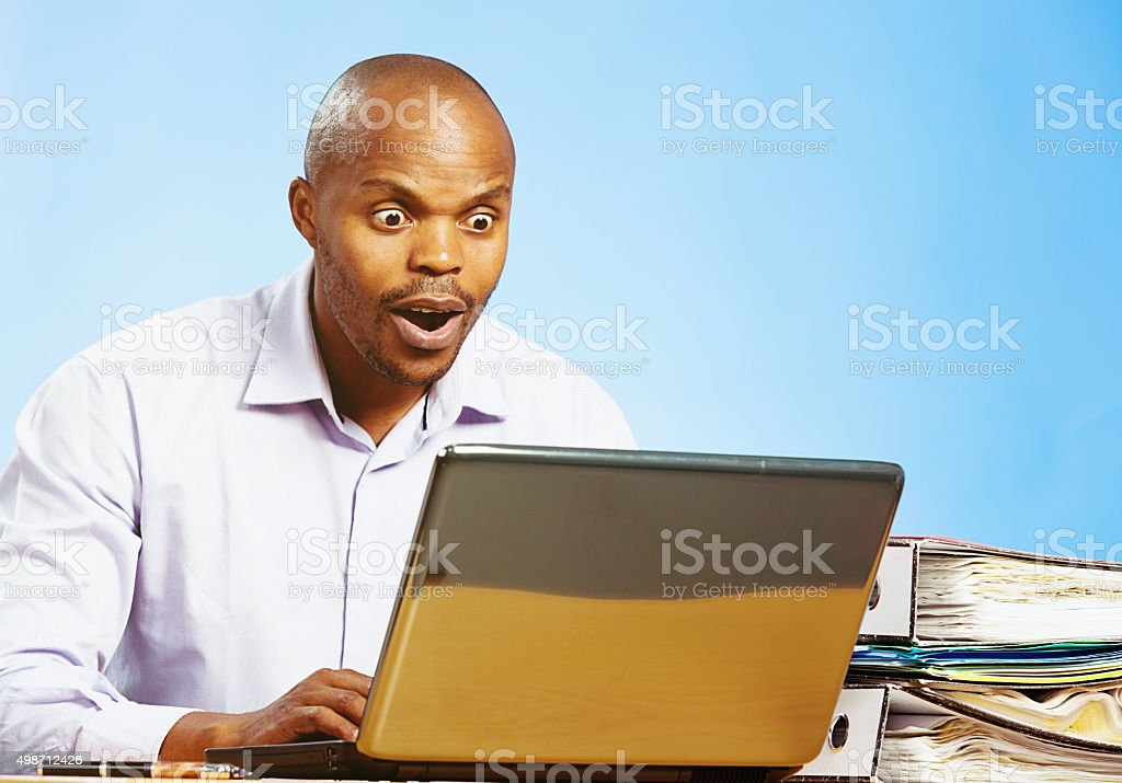 Shocked businessman staring at his laptop screen in horror stock photo