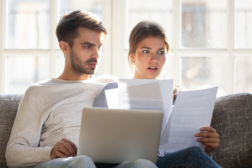istock Shocked by bad news couple sitting on couch reading letter 1138470080