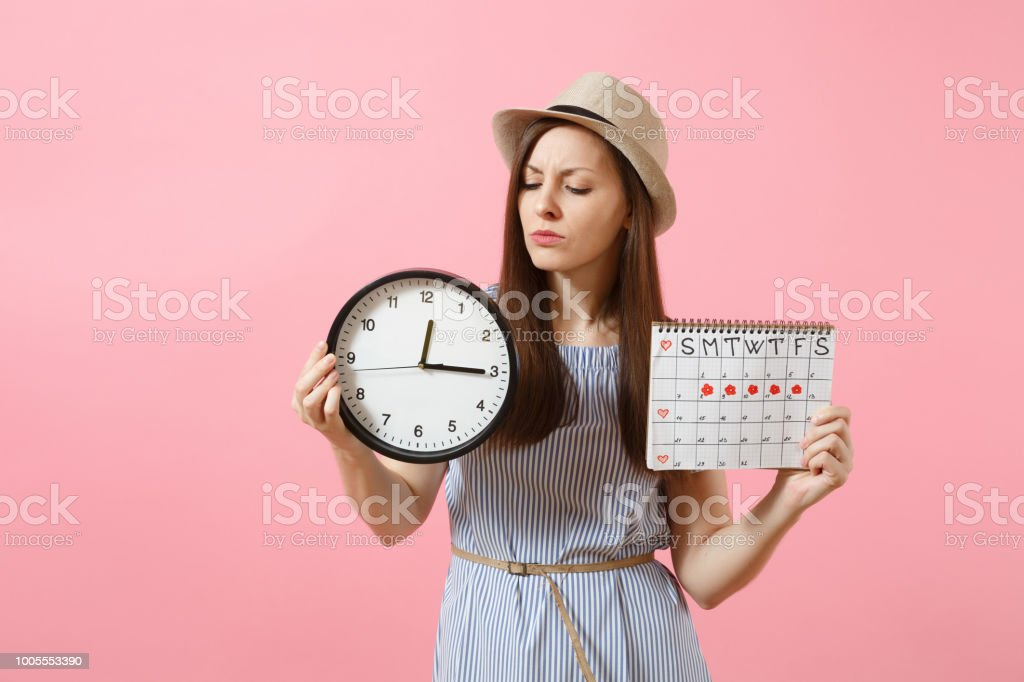 Shocked confused sad woman in blue dress holding round clock, periods...