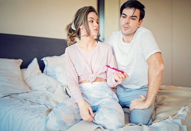 Shocked couple is looking positive pregnancy test in the bedroom stock photo