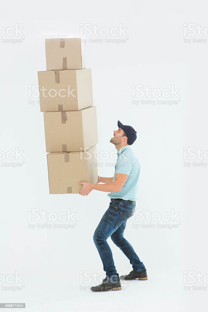 Shocked delivery man carrying stack of boxes stock photo