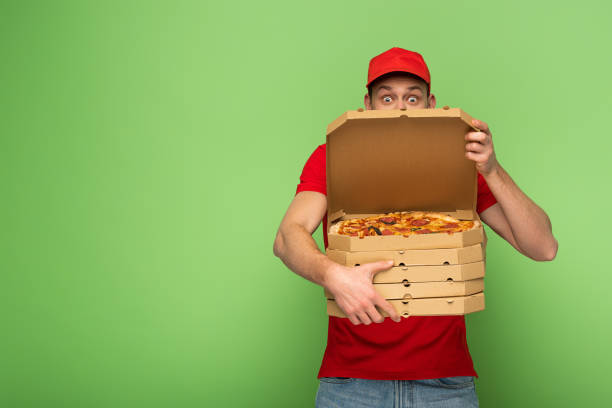 shocked delivery man in red uniform hiding behind pizza boxes on green stock photo