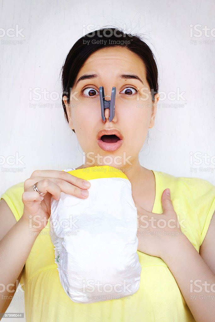 Shocked, disgusted woman holding up stinky diaper royalty-free stock photo