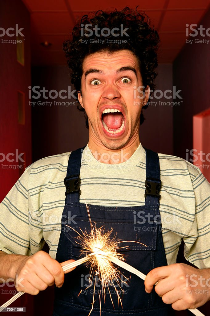 Shocked electrician holding sparkling wires with a short circuit stock photo
