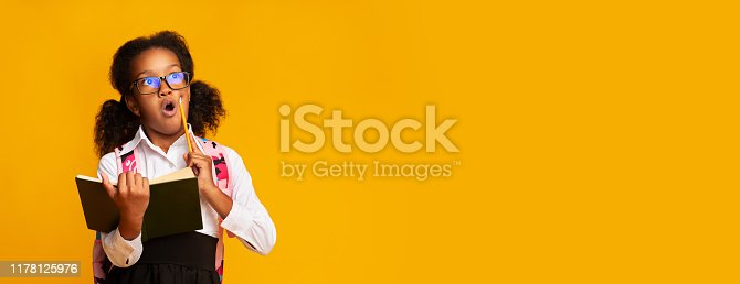 istock Shocked Elementary Student Girl Holding Schoolbook And Pencil, Studio Shot 1178125976