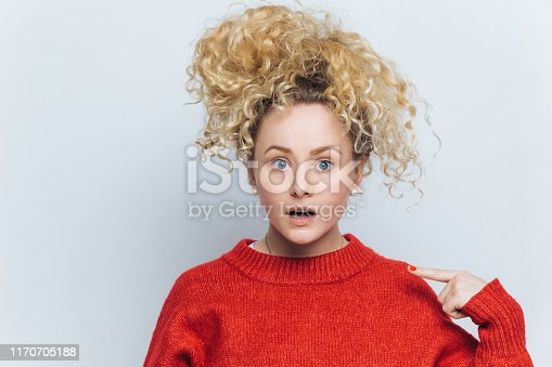 Shocked emotional amazed female stares at camera, indicates at sweater for your advertisment or information, isolated over white background. Surprised curly young woman isolated on white wall