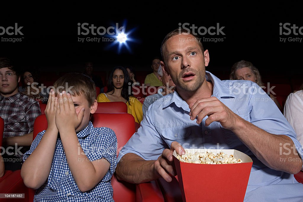Shocked father and son in movie theater royalty-free stock photo