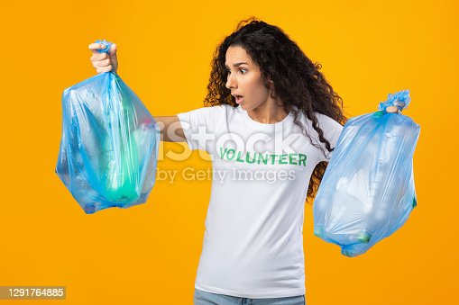 Shocked Female Volunteer Holding Unsorted Plastic Garbage Bags With Waste And Litter Standing Over Yellow Studio Background. Junk Sorting And Pollution Problem Concept
