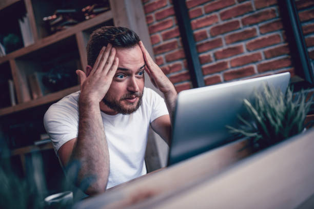 Shocked Freelancer in Disbelief Working at his Favorite Coffee Place Shocked Freelancer in Disbelief Working at his Favorite Coffee Place head in hands stock pictures, royalty-free photos & images