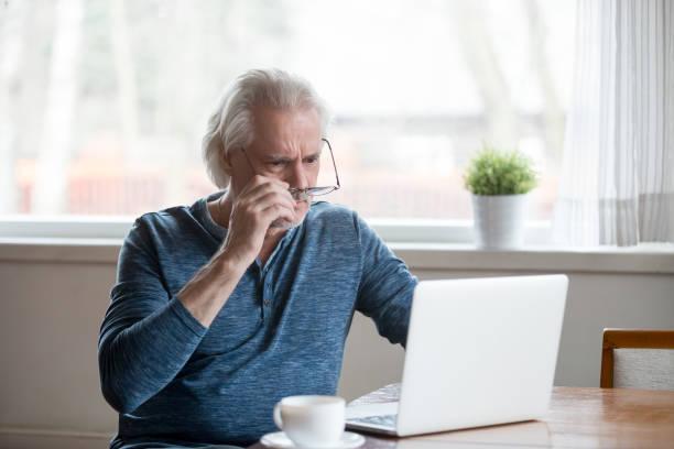 schockiert frustriert senior mann ausziehen gläser blick auf laptop - druckerzeugnis stock-fotos und bilder