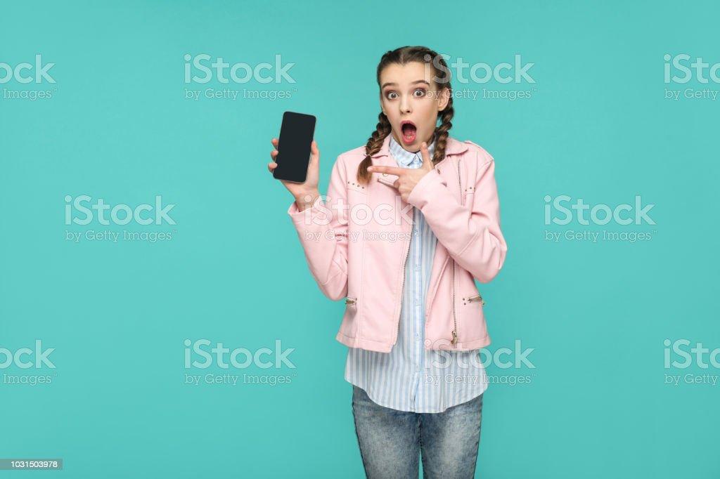 schockiert lustige Mädchen in Casual oder Hipster Stil, Zopf-Frisur, stehen, halten und zeigte auf mobile Display, Bildschirm mit überrascht Gesicht – Foto