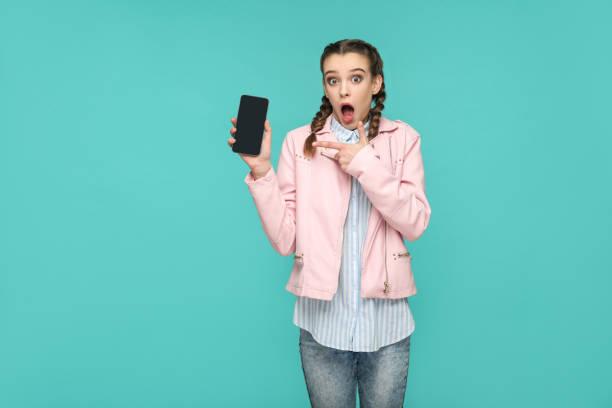 ピグテールの髪型、スタイル、カジュアルや流行に敏感なショックを受けて面白い女の子立って、保持、驚いた顔で画面のモバイル表示を指して、 - 見せる ストックフォトと画像