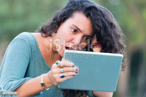 Shocked hispanic young woman looking at her Digital Tablet