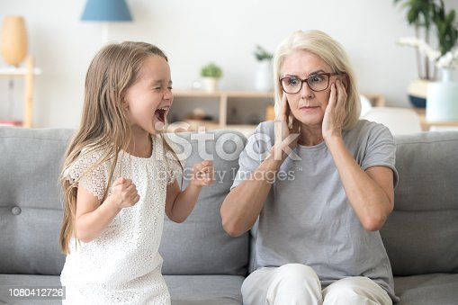 Shocked grandma closing ears not to hear noisy stubborn fussy little granddaughter screaming demanding attention, preschool spoiled kid girl yelling at grandmother, child tantrum manipulation concept