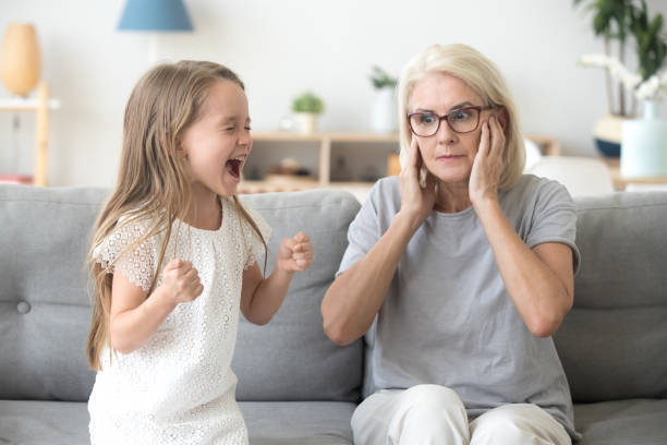 geschokt oma oren sluiten niet te horen koppig kleindochter schreeuwen - roepen stockfoto's en -beelden