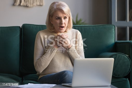 istock Shocked grey haired mature woman reading unexpected news on laptop 1147376466