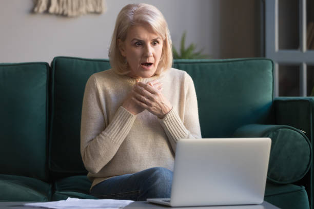 Shocked grey haired mature woman reading unexpected news on laptop Shocked grey haired mature woman with wide opened eyes reading unexpected online news on laptop, sitting on couch, looking at screen, stressed middle aged female receiving bad email, computer problem shocked computer stock pictures, royalty-free photos & images