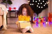 istock Shocked happy african american little girl enjoying Christmas gift 1191434866