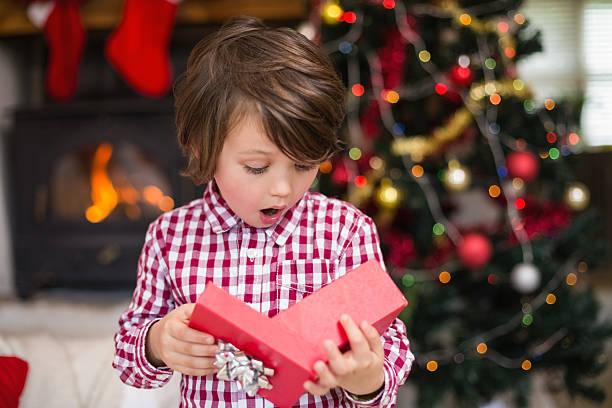 überrascht kleine junge auf der suche in geschenk - weihnachten 7 jährige stock-fotos und bilder
