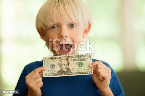Portrait of shocked little boy in blue t-shirt holding a twenty Dollar bill